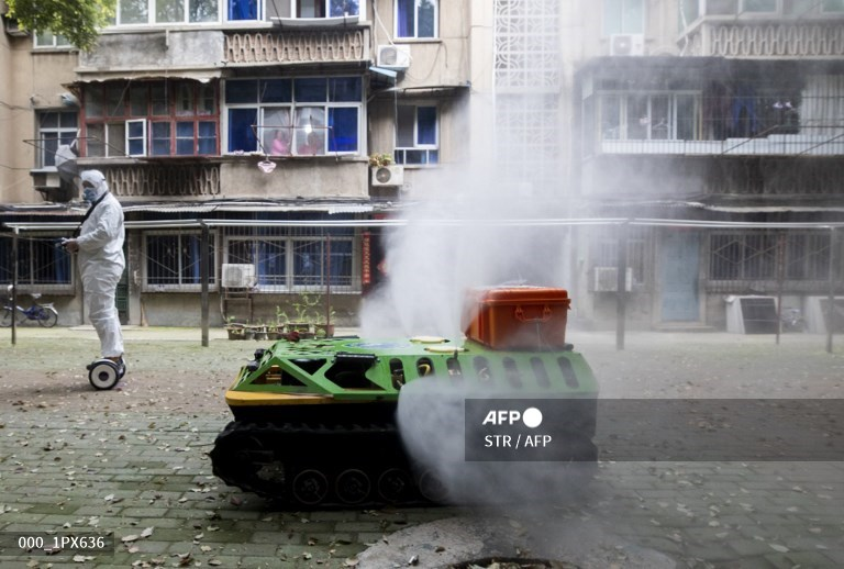 A volunteer operates a remote controlled disinfection robot to disinfect a residential area. Source: AFP